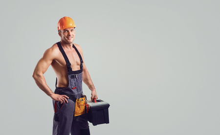 Photo pour Sexy repairman in helmet smiling at the special clothes with a working tool on a gray background. - image libre de droit