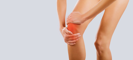 Photo for Pain, injury to the knee. A woman holds her knee with her hand. - Royalty Free Image