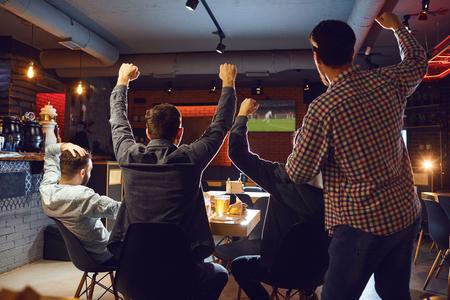Foto de Friends watch sport tv in the pub. Young people support their team in the bar. - Imagen libre de derechos