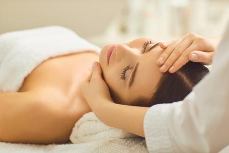 Photo pour Spa treatment at beauty salon. A young woman gets a facial massage at the cosmetology center. - image libre de droit
