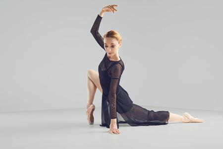 Ballerina in a black tutu elegantly dancing on a black background. Concept ballet dancing dancer.