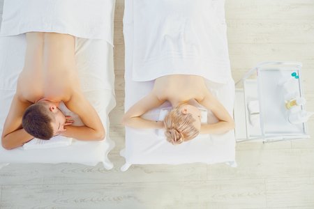 Photo pour From above shot of man and woman lying on tables and enjoying massage with masseur - image libre de droit