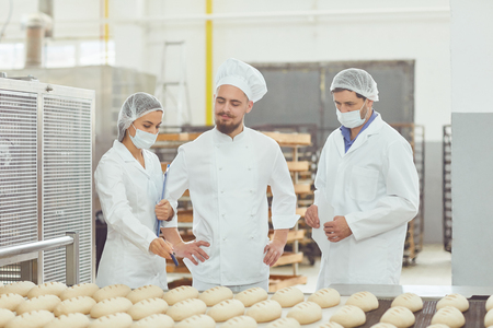 Photo for Technologist and baker inspect the bread production line at the bakery. - Royalty Free Image