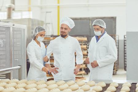 Photo pour Technologist and baker inspect the bread production line at the bakery. - image libre de droit