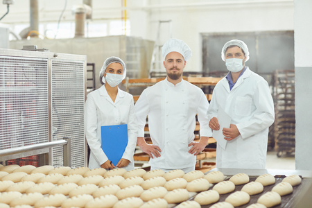 Photo pour Technologist and baker inspect the bread production line at the bakery. - image libre de droit