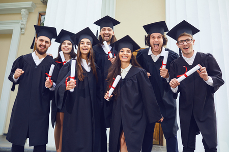 Photo pour A group of graduates with scrolls in their hands are smiling against the background of the university. Graduation.University gesture and people concept. - image libre de droit