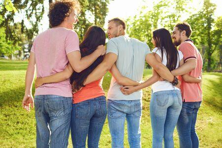 Foto de Young people hug in the park in nature. Back view. - Imagen libre de derechos