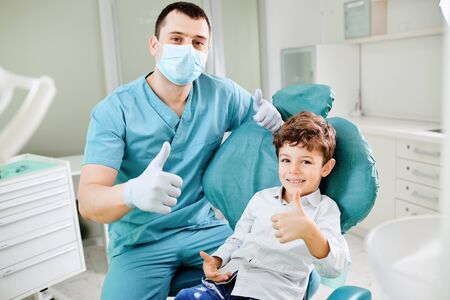 Photo pour Happy dentist and child raised their thumb up at the dental clinic. - image libre de droit