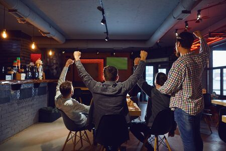 Photo pour Friends in the sports bar support their team watching TV. - image libre de droit