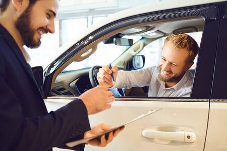 Photo pour A young woman buys a car in a car showroom. A man signs a car rental agreement. - image libre de droit