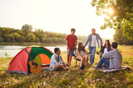 Photo pour A group of friends have a picnic in a forest near a lake in the summer in autumn. - image libre de droit