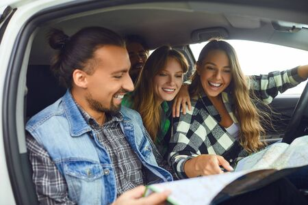 Photo pour A group of happy friends travelers choose the route on the map ride in the car. - image libre de droit