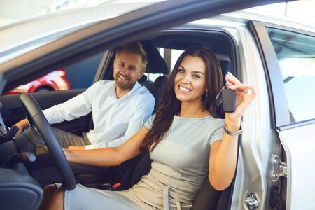 Photo pour A happy couple bought a new car at a car showroom. Buying and renting cars. - image libre de droit