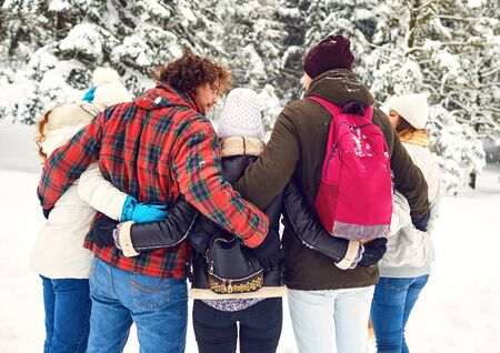 Photo pour Friends embracing in the woods in winter from the back - image libre de droit