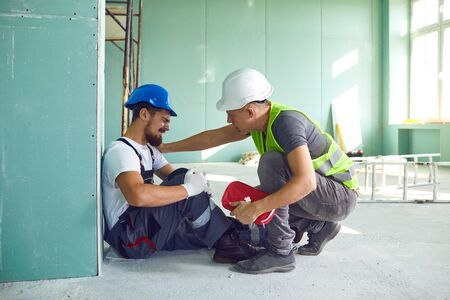 Photo for Construction worker accident with a construction worker. First aid for injury at work. - Royalty Free Image