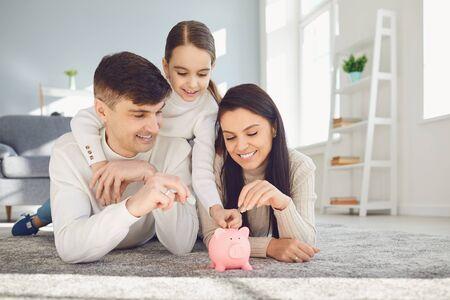 Photo pour Happy family saves money in a piggy bank pig. Money finance saving concept. - image libre de droit