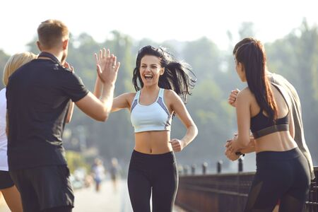 Foto de Girl runner runs fun with a group of friends in a park in the morning in the summer in autumn. Active lifestyle. Jogging. Health. Healthy lifestyle. - Imagen libre de derechos