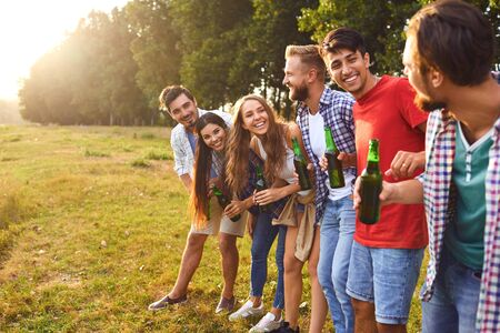Photo pour Young smiling people drink glasses at a picnic in a forest near a lake in the summer in the autumn. - image libre de droit