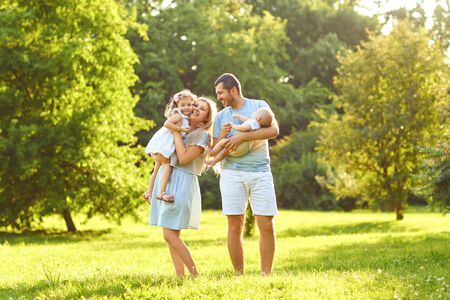 Foto de Family with baby stands on green grass in the park with sunlight in summer. The concept of a happy family. - Imagen libre de derechos