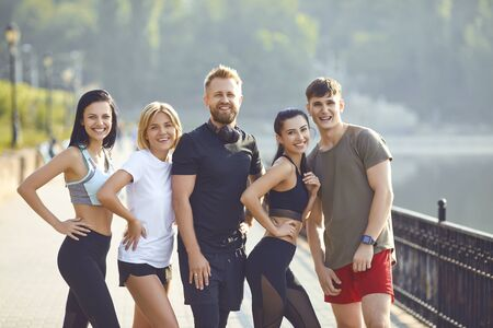 Foto de A group of athletes training in the park. Friends in sportswear portrait standing outdoors in the morning. Healthy lifestyle. - Imagen libre de derechos