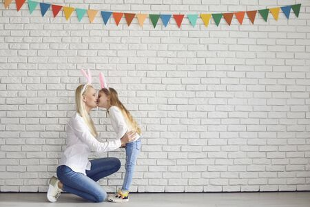Photo pour Happy easter. Mother and daughter with rabbit ears are standing smiling against a white brick wall. - image libre de droit
