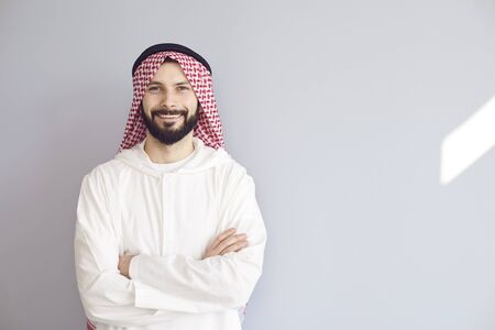Photo pour Attractive smiling arab man crossed his arms on a gray background for text. - image libre de droit