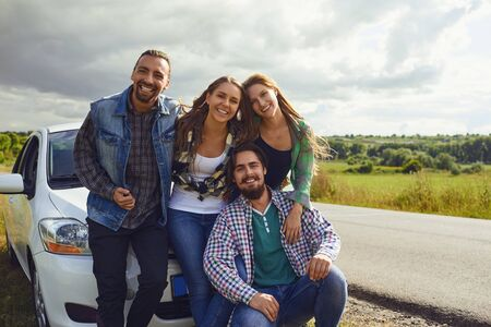 Photo pour Group of happy people standing next travel in the car on road. - image libre de droit