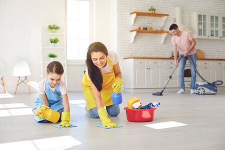 Photo pour Happy family cleans the room in the house. Mother and little daughter wash in gloves while sitting on the floor smiling joyful. Hygiene Wash. - image libre de droit