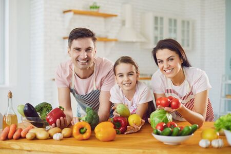 Photo for Beautiful happy family smiling at a table with fresh vegetables make salad in the kitchen. Mother father and little daughter make healthy food fresh vegetables in room. - Royalty Free Image