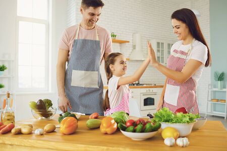Photo for Happy family with kid preparing fresh vegetables on the table in the kitchen. Healthy eating. Parents with daughter cut a salad with a knife in the kitchen in the house. - Royalty Free Image