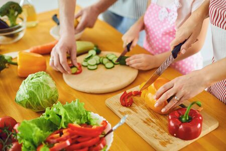 Faceless. Family hands prepare fresh vegetables salad on the table in the kitchen. Mother's hands cut vegetables with a knife. Healthy eating