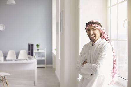 Photo pour Arab man businessman smiling stands in a white office. - image libre de droit