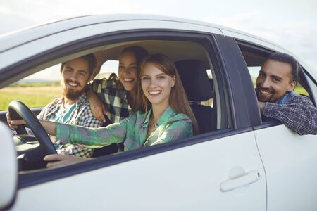Photo pour A group of happy smiling friends travelers are driving in a car on road. - image libre de droit