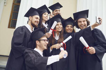 Photo pour Students graduates are photographed on the phone at the university college. Graduation.University gesture and people concept. - image libre de droit