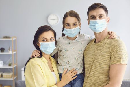 Photo for Family in medical masks on the face looks at the camera while standing in the room at home. The concept of quarantine protection self-isolation virus pandemic coronavirus. - Royalty Free Image