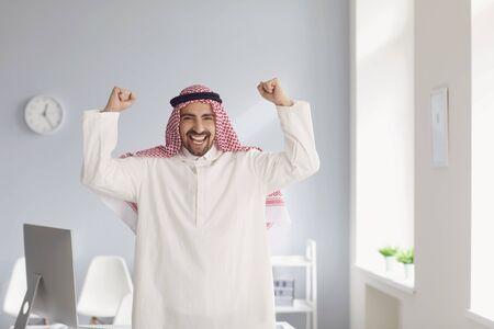 Photo pour Positive smiling arabic businessman rejoices raised his hands up in a white office bright room. - image libre de droit