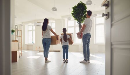 Photo pour Smiling family is laughing while standing in a sunny new home.Back view. The concept of moving estate new apartment house move home buy sale property rent room investment . - image libre de droit
