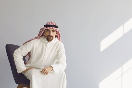 Photo pour Pensive serious arab businessman sitting in a chair thinks looks up on a gray background. Portrait of an attractive arab man. - image libre de droit