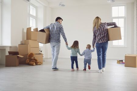 Photo for Happy family with children moving with boxes in a new apartment house. Relocation concept new house apartment rental housing. - Royalty Free Image
