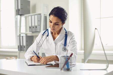 Photo pour Confident woman doctor pediatrician writes in a clipboard sitting at a table in a white office of the hospital. - image libre de droit