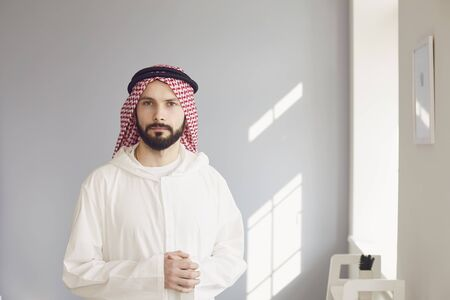 Photo pour Arab male businessman smiling portrait standing on a gray background. - image libre de droit