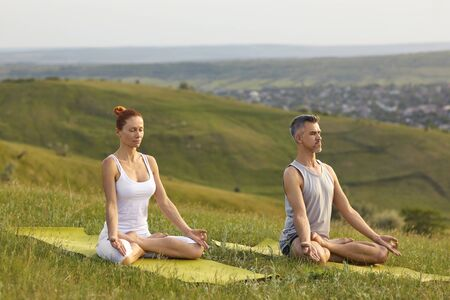 Photo pour Practice yoga meditation. A mated couple practices yoga meditation in lotus position sitting on the grass on the nature of the countryside in summer spring. - image libre de droit