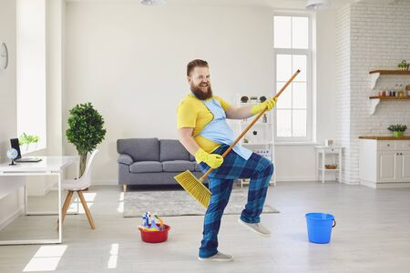 Photo pour Side view of childish male in apron and rubber gloves pretending playing guitar while standing with cleaning brush in living room and looking at camera. - image libre de droit