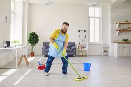 Photo pour Funny fat man in an apron and yellow cleaning gloves is cleaning the house in the room. - image libre de droit