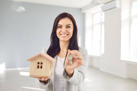 Photo pour Woman seller broker realtor agent is a realtor with keys in hand against the background of a white real estate room apartment home. Sale purchase rent real estate mortgage. - image libre de droit