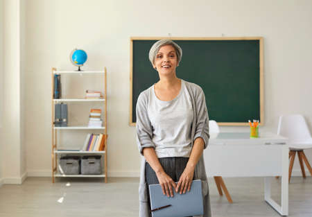 Foto de The teacher in the classroom. A woman with gray hair mature teacher with a notebook in her hand looks at the camera standing on the background of the class. - Imagen libre de derechos