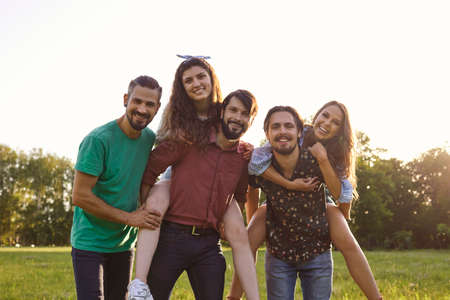 Photo pour Group of happy friends piggyback ride laughing hugging on nature in summer in spring.Cheerful friends play fooling around together in a park. - image libre de droit