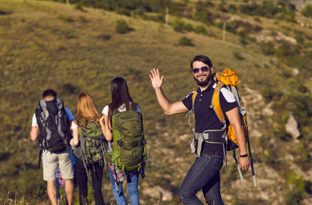 Photo pour A group of hikers with backpacks are walking along the hill in the mountains in nature. Travel adventure people tourists. - image libre de droit