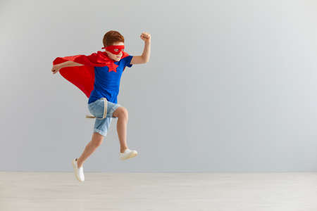 Photo pour Happiness, freedom, childhood, movement and people concept, boy in red superhero cape and mask jump and fly. - image libre de droit