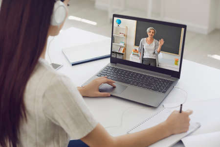 Foto de Learning education course lecture online. Girl student in headphones listens to the teacher video chat application remotely at home. - Imagen libre de derechos